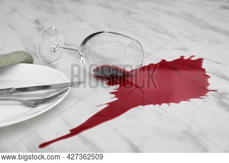 Overturned Glass And Spilled Red Wine On White Marble Table