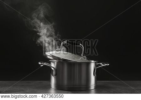 Steaming Saucepot On Grey Table Against Dark Background