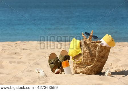 Bag With Beach Accessories And Slippers On Seaside. Space For Text
