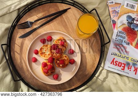 Delicious Cottage Cheese Pancakes With Fresh Raspberries And Juice Served On Bed Tray, Flat Lay