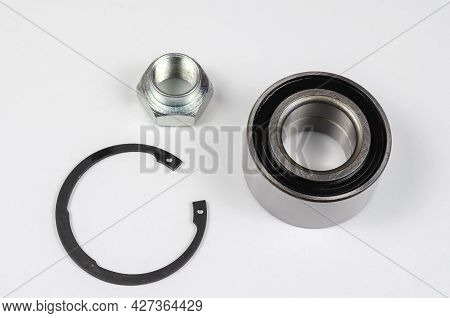 Set Of Auto Parts On White Background. New Retaining Ring, Special Nut And Hub Bearing.  Spare Parts