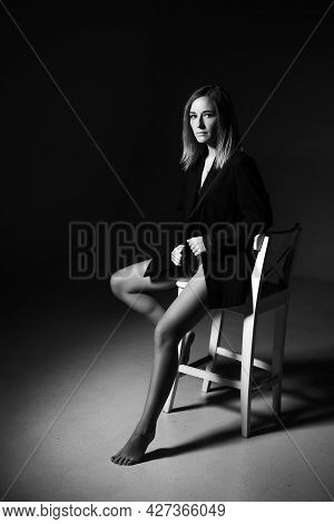 Beautiful Woman Of Caucasian Ethnicity Posing Sitting On A Chair In A Black Jacket And Lingerie, Bla