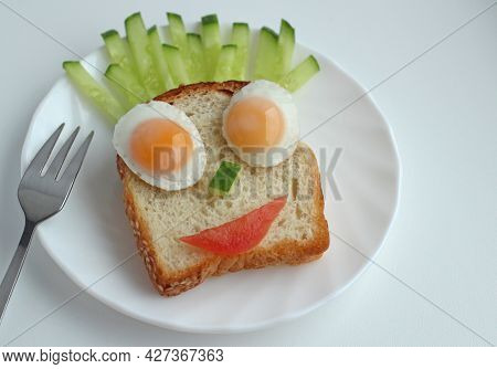 Childrens Breakfast Piece Of Bread With Fried Egg And Fresh Vegetables