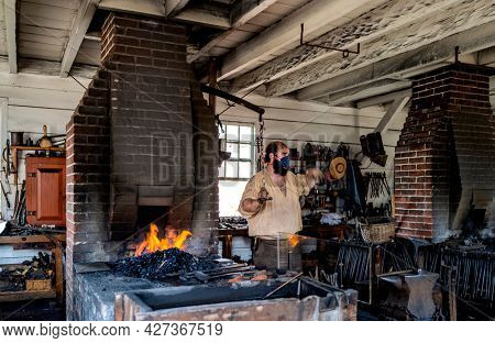 Williamsburg, Virginia, USA: 29th March 2021; A blacksmith working an old metal forge in colonial Williamsburg