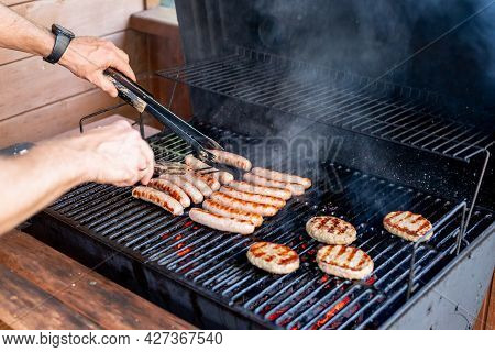 Grilling At Summer Weekend. Fresh Meat Preparing On Grill.man Hand At A Barbecue Grill Preparing Mea