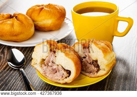 Small Fried Pies With Meat Filling (belyash) In White Plate, Teaspoon, Halves Of Pie In Yellow Sauce