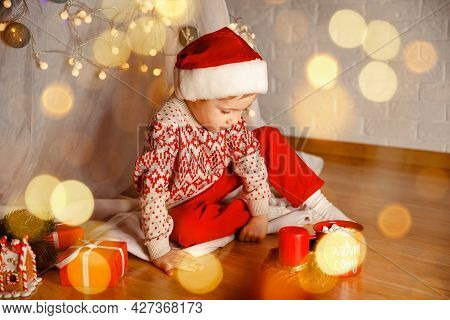 Cute Little Child Kid With Red Present Gift Box Indoor. Happy Boy Unwrapping His Xmas Gifts At Home.