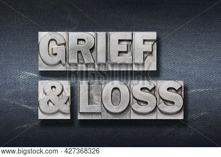 Grief And Loss Phrase Made From Metallic Letterpress On Dark Jeans Background