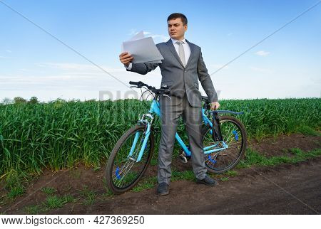 Businessman with a bicycle works with documents in a green grass field - business concept for freedom, vacation or freelance. Beautiful spring nature.