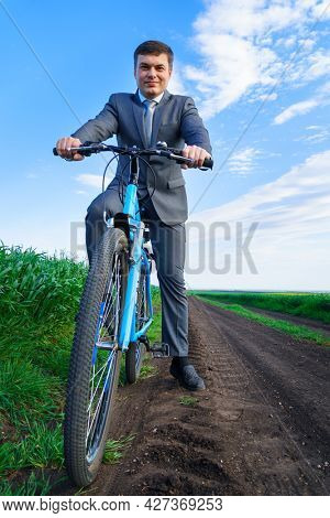Businessman with a bicycle posing in a green grass field - business concept for freedom, vacation or freelance. Beautiful spring nature.