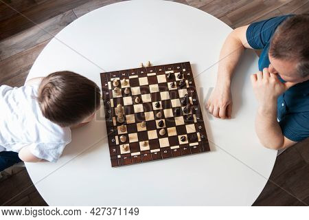 View From Above Dad And Son Are Playing A Board Game Of Chess. Time And Games With Children. Logic A