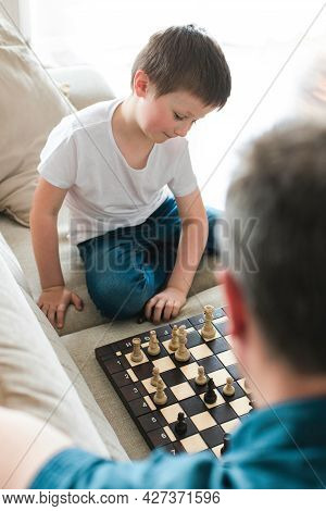 Dad And Son Are Sitting On The Couch And Playing Chess. Leisure With Children, Pastime And Games.