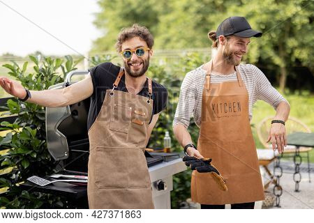Portrait Of A Two Handsome Male Friends In Aprons Have Fun While Grilling Meat For Burgers On Gas Gr