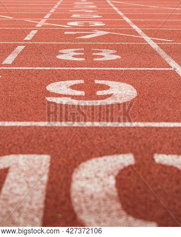Sideview On Lane Numbers At The Finish Of Red Race Track (running Track Or Athletics Track), Shallow