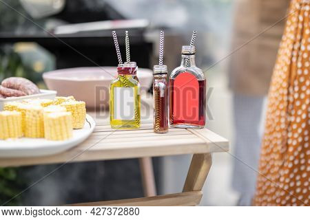 Bottles With Liqueur Or Berry Tinctures On A Table With Food For Bbq, People Grilling On A Backgroun