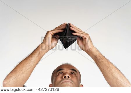 Upset Mature Man Holding Upside Down And Looking Inside His Empty Wallet On White Background. Financ
