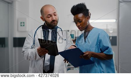 Practitioner Doctor With Afro American Assistant Analyzing Recovery Treatment Using Tablet Computer