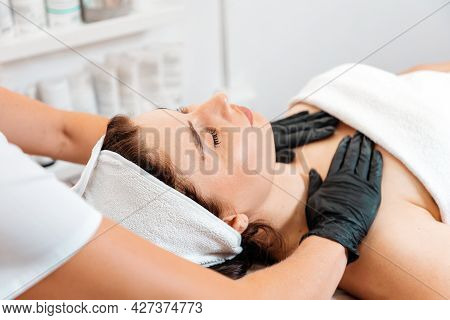 Concept Of Lifting And Beauty Procedures. Professional Cosmetologist Gives A Facial Massage To The C