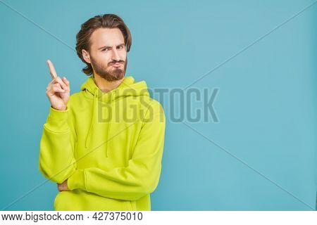 Young emotional man disappointed looking at the camera. People, emotions. Studio portrait on a blue background with copy space.