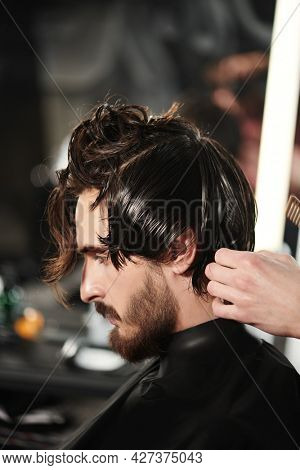 Barbershop. Portrait of a handsome man with dark hair, beard and mustache getting his hair cut in a barbershop.