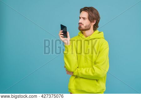 Studio portrait young disappointed man holding phone on a blue background with copy space. People, emotions.