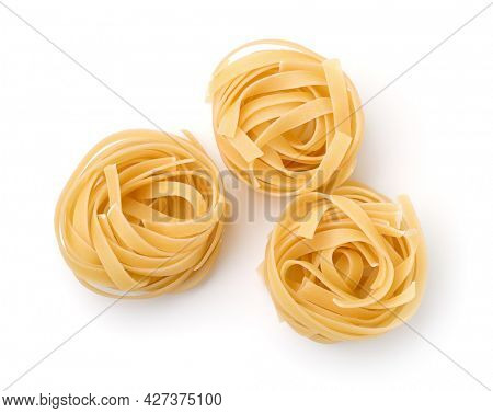 Top view of three uncooked tagliatelle ribbon pasta nests isolated on white