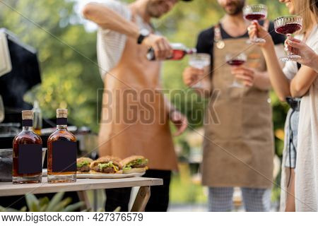 Young People With Alcohol Drinks At Picnic, Pouring Wine Or Liqueur Into A Glasses. Image Focused On