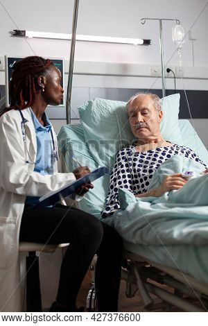 African American Doctor Reading Diagnosis From Clipboard To Sick Ill Unwell Senior Patient Laying In