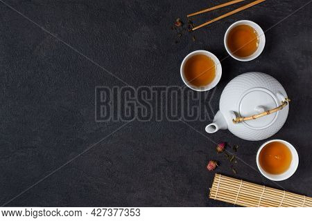 Teapot And Tea Cups With Tea Drink Top View On Black Background. Asian Tea Ceremony.