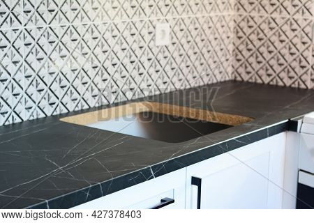 New Kitchen Furniture Installation With A Close-up Of A Tiled Kitchen Backsplash With An Electric So