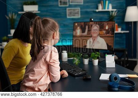 Parent And Little Kid Meeting With Grandma On Video Call Virtual Communication. Family Of Two Using