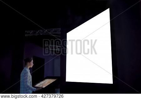 Woman Using Electronic Kiosk And Looking At Large Wall Blank White Display In Dark Room Of Science E