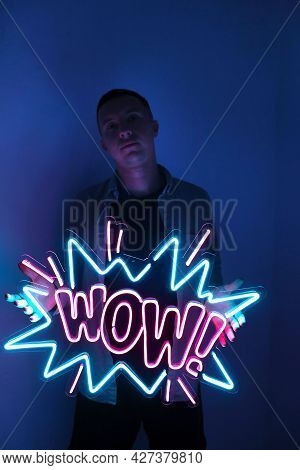 A Handsome Guy Is Holding A Neon Wow Sign In Pink And Blue. Trendy Style. Wow. Neon Sign. Custom Neo