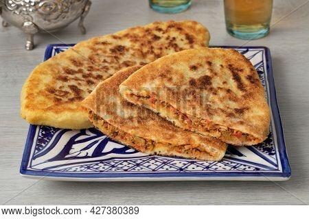 Plate with traditional fresh baked whole and half Moroccan stuffed batbot and tea