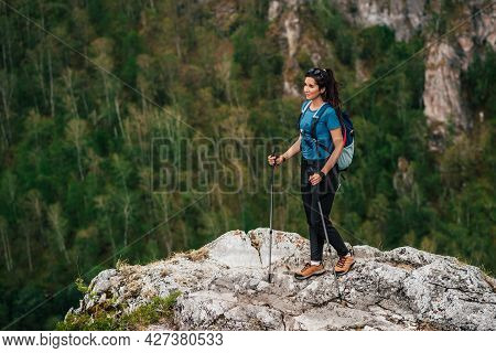 Hiking In The Mountains. The Concept Of Active Recreation. Traveling Woman With A Backpack On The Ba