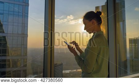 Portrait Of Woman Using Smartphone Device Against Sunset Cityscape View Through Window Of Skyscraper
