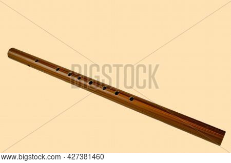 Brown Bamboo Flute Instrument Isolated On A Soft Yellow Background.