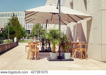 Cafe With A Summer Terrace. Umbrellas, Tables And Tropical Plants