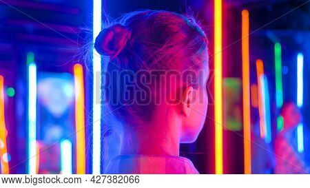 Back View - Portrait Of Woman Looking Right At Interactive Exhibition Or Museum With Colorful Fluore