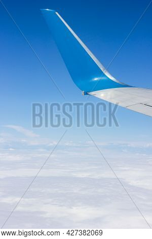 Plane Tail Blue Sky And White Clouds Aerial View From Plane Window, Theme Of Air Travel And Travel,