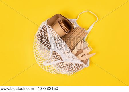 Kraft Paper Food Cups, Plates And Containers With Wooden Cutlery In Cotton Bag On Yellow Background