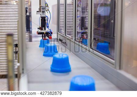 Blue Polypropylene Pots On Conveyor Belt Of Automatic Plastic Injection Molding Machine With Robotic