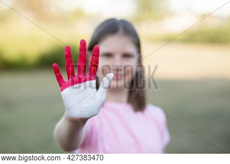 Girl With Open Hand Raised, Painted In Indonesia Flag Color, Focus On Hand. Girl Show Stop Gesture W