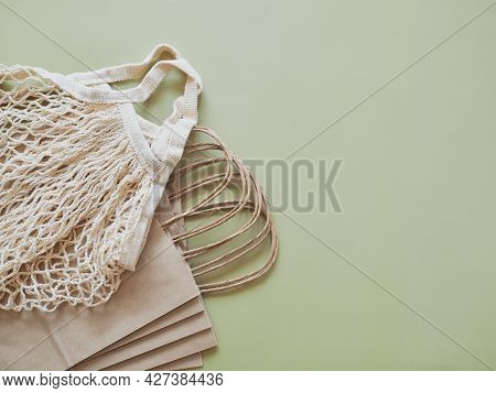 Biodegradable Paper Bags And Reusable Mesh Cotton Shopper On Neutral Green Background. Eco Friendly