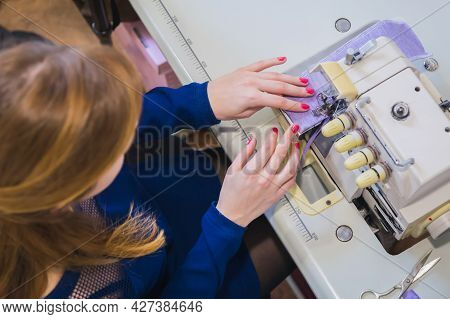 Professional Tailor, Seamstress Sitting And Using Overlocking Sewing Machine - Top View. Fashion And