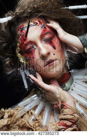 A young woman in a zombie costume - wrapped in bandages and with syringes in her hair. Creative image for the party.