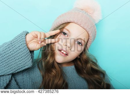Pleased Young girl in sweater and hat looking at the camera, studio shoot