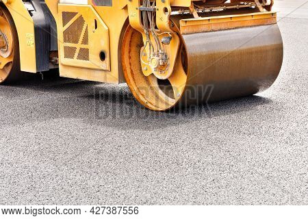 The Metal Cylinder Of The Yellow Road Vibrating Roller Compacts The Fresh Asphalt Powerfully On The