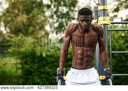 Young Athlete Afroamericatsen, Exercising On The Uneven Bars, An Athlete In Excellent Physical Shape
