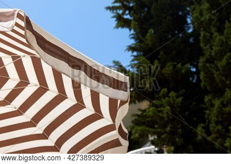 Striped Sun Umbrella Against A Background Of Blue Sky And Green Trees. Concept Of Summer Hotel Holid